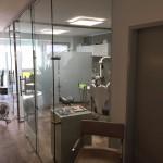 Behandlungszimmer einer Zahnarztpraxis mit Glas abgetrennt